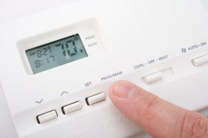 hand-adjusting-thermostat